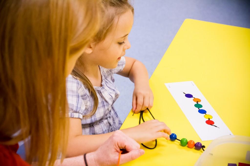 little girl stringing beads